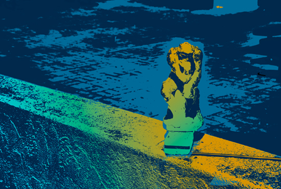 Photo rendered in gold and blue tones showing the reproduction of Rodin's Thinking Man outside the department of Communication