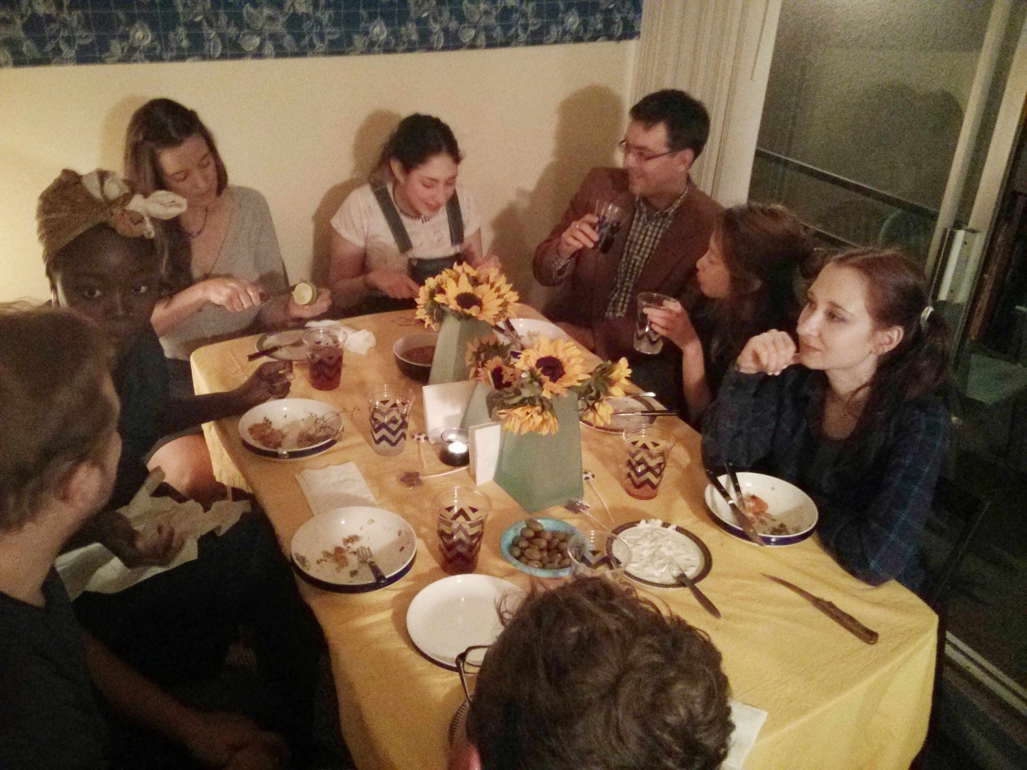 first year graduate students eating dinner in a home environment hosted by second year students. sunflower and yellow decorations.