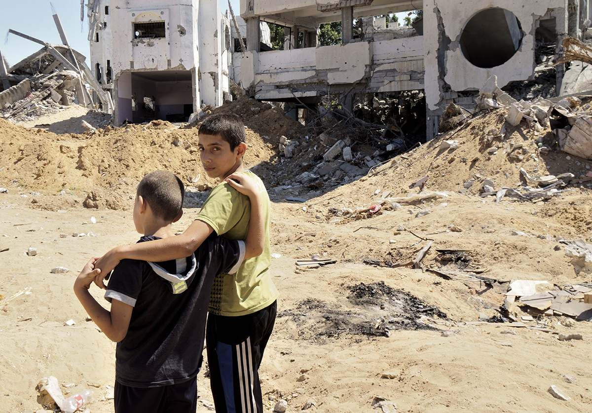 Two brothers in front of their house in the Shuja'iya neighborhood destroyed during Operation Protective Edge (2014).  Photo by Gary Fields